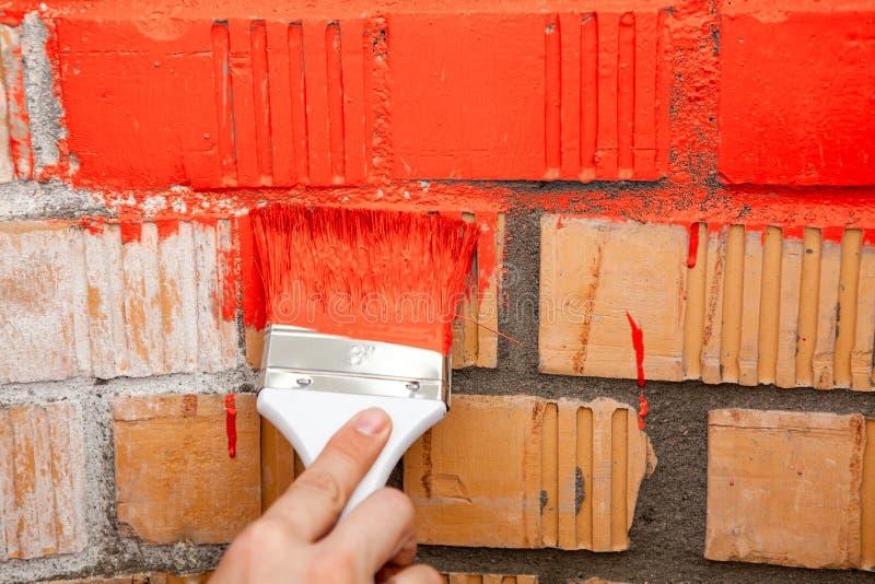 Βούρτσα χρωμάτων με το κόκκινο χρώμα στο τουβλότοιχο στοκ εικόνα με δικαίωμα ελεύθερης χρήσης