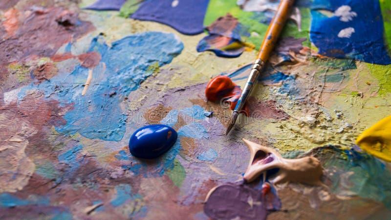Βούρτσα χρωμάτων με το υγρό ακρυλικό χρώμα σε έναν λεκιασμένο χρώμα καμβά στοκ εικόνα