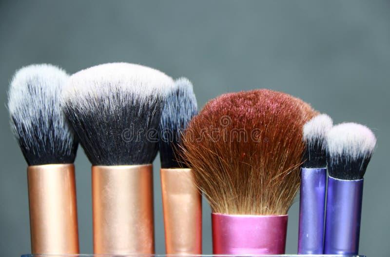 Βούρτσα Makeup στην πορφυρή, ρόδινη και χρυσή λαβή χρώματος Είναι δειγμένο ίδρυμα στοκ φωτογραφία με δικαίωμα ελεύθερης χρήσης