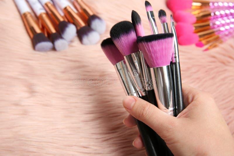 Βούρτσες εκμετάλλευσης γυναικών makeup πέρα από το γούνινο ύφασμα r στοκ εικόνες με δικαίωμα ελεύθερης χρήσης