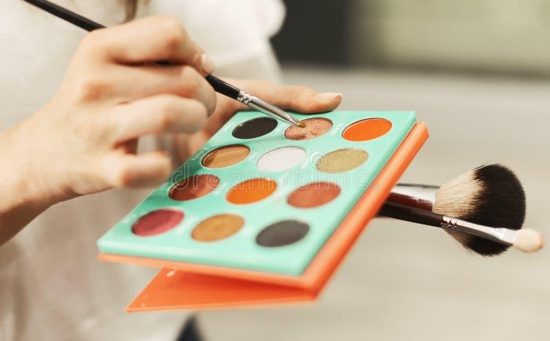 Βούρτσες εκμετάλλευσης χεριών του καλλιτέχνη Makeup και παλέτα σκιάς ματιών, κινηματογράφηση σε πρώτο πλάνο στοκ εικόνες