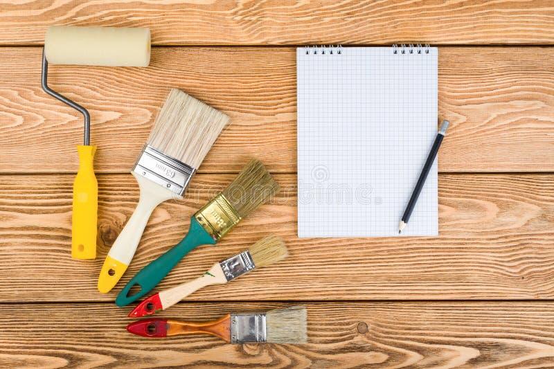 Βούρτσες, κύλινδρος και σημειωματάριο χρωμάτων στοκ εικόνα