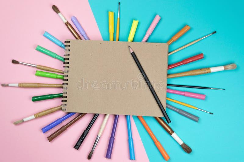 Βούρτσες, χρωματισμένα μολύβια, χλεύη σημειωματάριων επάνω για το έργο τέχνης στοκ φωτογραφία