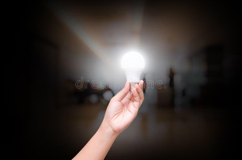 Βολβός των οδηγήσεων φωτισμού λαβής χεριών γυναικών στη μουτζουρωμένη εσωτερική αίθουσα offic στοκ φωτογραφία με δικαίωμα ελεύθερης χρήσης