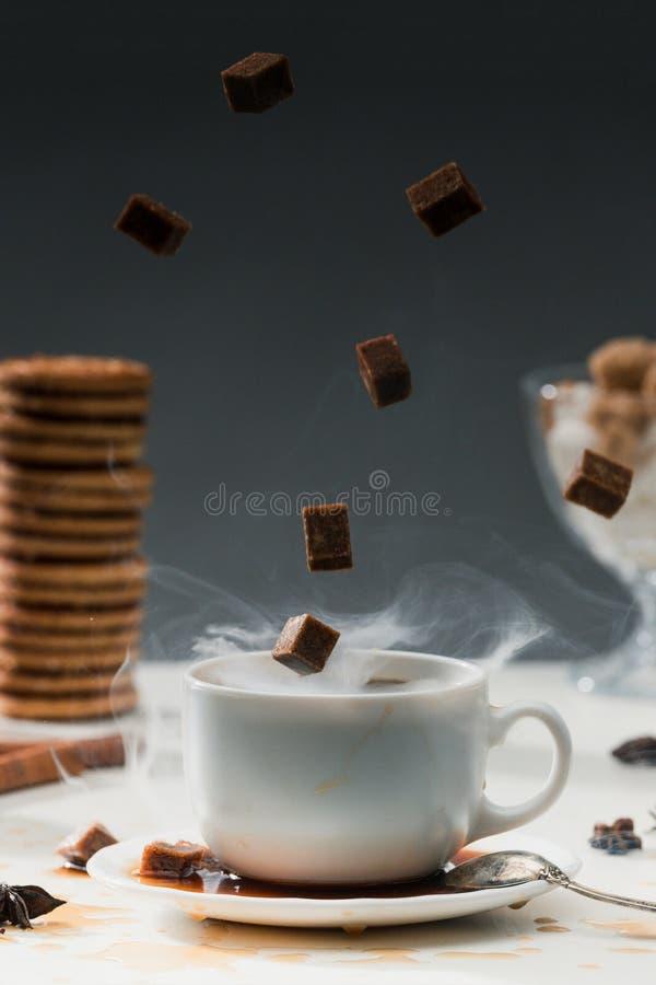 Βράσιμο στον ατμό του φλυτζανιού καφέ με τους μειωμένους κύβους ζάχαρης καλάμων από τα μπισκότα στοκ εικόνες