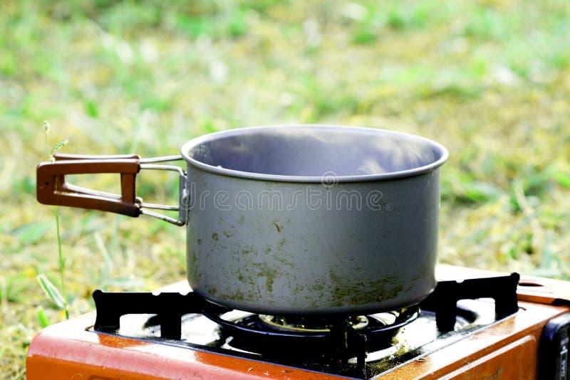 Βράστε κάτι στο δοχείο στη σόμπα αερίου στο υπόβαθρο χλόης στοκ φωτογραφία