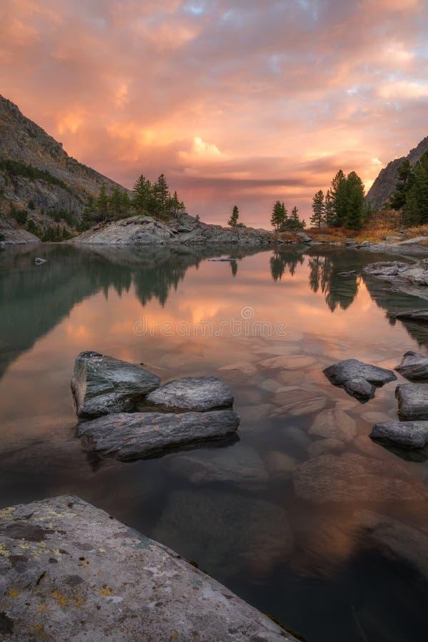 Βράχοι και δέντρα που απεικονίζουν στα ρόδινα νερά της λίμνης βουνών ηλιοβασιλέματος, τοπίο φθινοπώρου φύσης ορεινών περιοχών βου στοκ φωτογραφίες με δικαίωμα ελεύθερης χρήσης