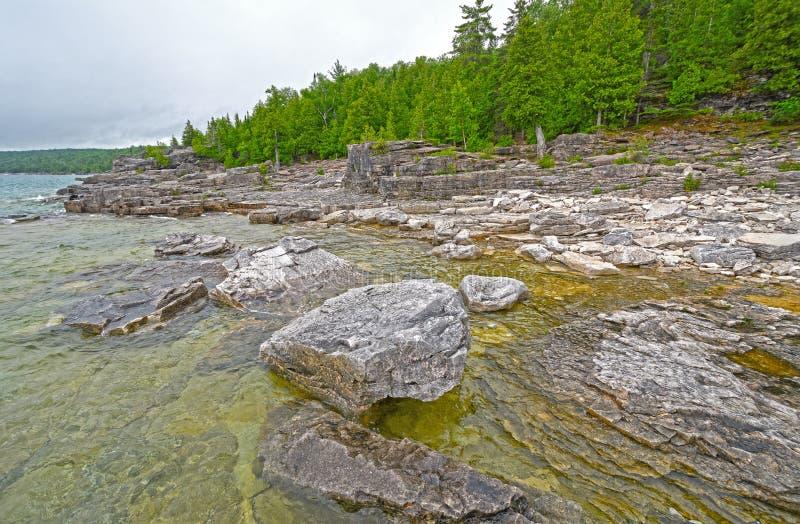 Βράχοι και πεύκα σε ένα μακρινό Lakeshore στοκ εικόνα