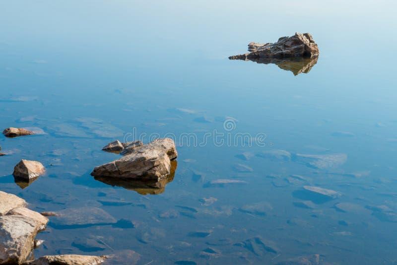 Βράχοι στο μπλε ήρεμο νερό στοκ εικόνες