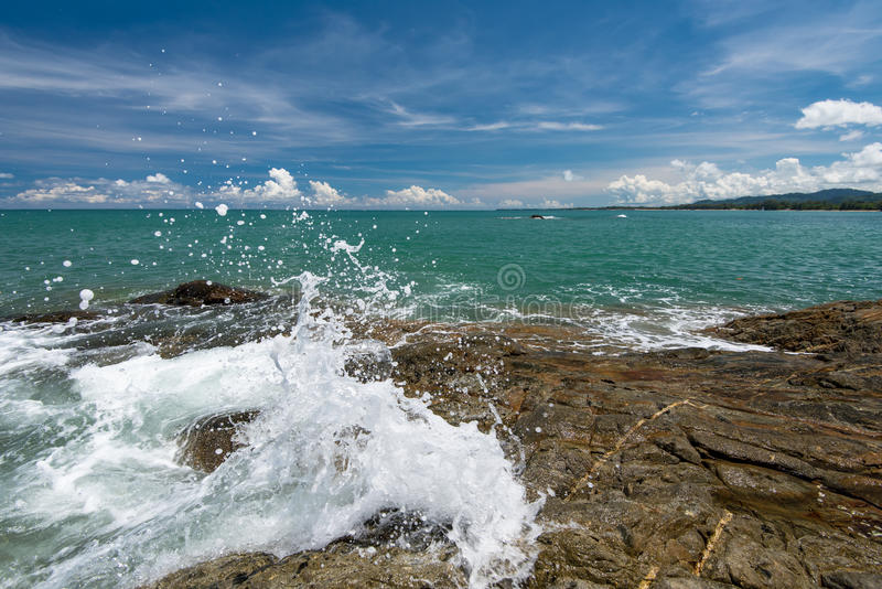 Βράχος αντίκτυπου γραμμών μαστιγίων κυμάτων θάλασσας στην παραλία κάτω από το μπλε ουρανό στοκ φωτογραφίες