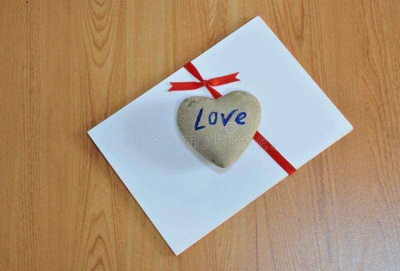 Download Βράχος καρδιών στην κόκκινη κορδέλλα δεσμών της Λευκής Βίβλου Στοκ Εικόνα - εικόνα από πέτρα, καρδιά: 62714027