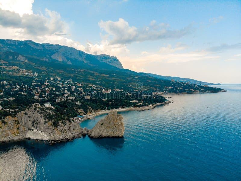 Βράχος στην μπλε θάλασσα Της Κριμαίας βουνά στο υπόβαθρο στοκ φωτογραφία