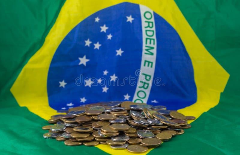 Βραζιλιάνα νομίσματα, στη σημαία υποβάθρου της Βραζιλίας Οικονομική πραγματικότητα στοκ εικόνα με δικαίωμα ελεύθερης χρήσης