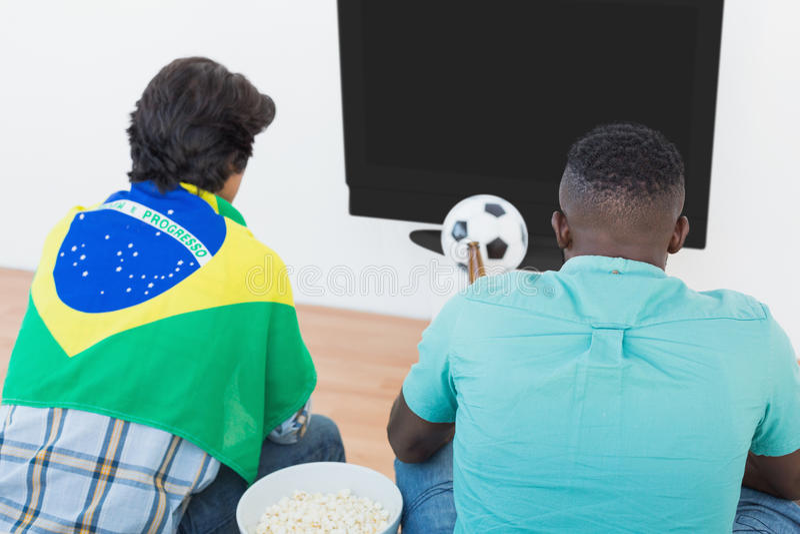 Βραζιλιάνοι ανεμιστήρες ποδοσφαίρου που προσέχουν τη TV στοκ εικόνες