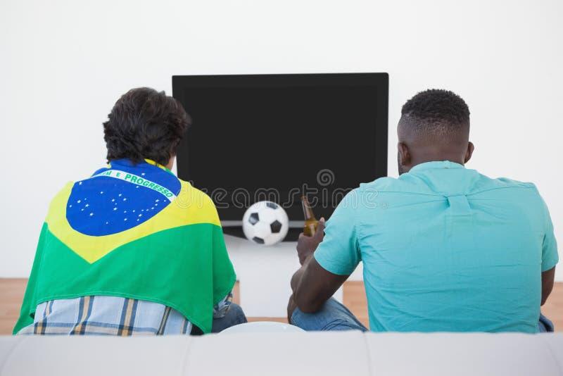 Βραζιλιάνοι ανεμιστήρες ποδοσφαίρου που προσέχουν τη TV στοκ φωτογραφία με δικαίωμα ελεύθερης χρήσης
