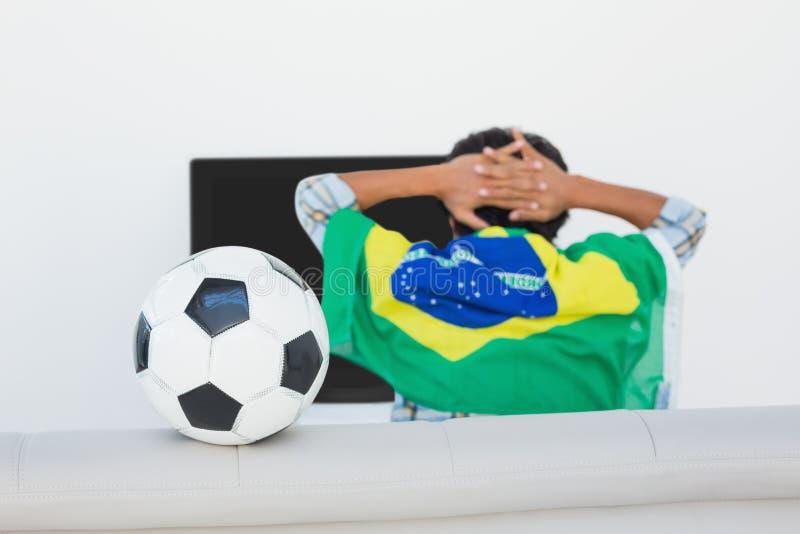 Βραζιλιάνος ανεμιστήρας ποδοσφαίρου που προσέχει τη TV στοκ εικόνες