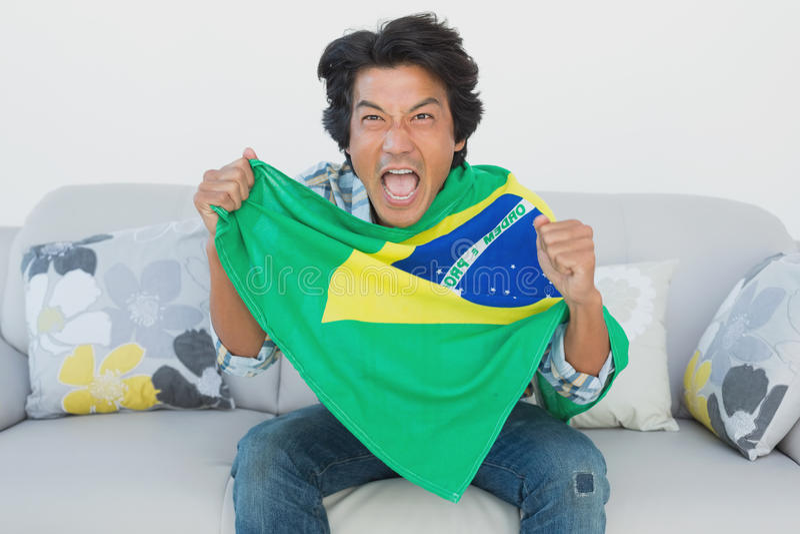 Βραζιλιάνος οπαδός ποδοσφαίρου ενθαρρυντικός προσέχοντας τη TV στοκ φωτογραφία