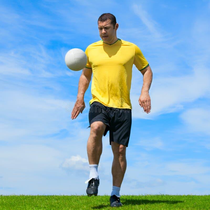 Βραζιλιάνος ποδοσφαιριστής ποδοσφαίρου που κάνει το kicky UPS στοκ φωτογραφίες