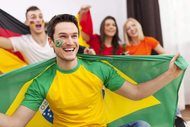 Βραζιλιάνο άτομο με τους φίλους της ενθαρρυντικούς στοκ φωτογραφία