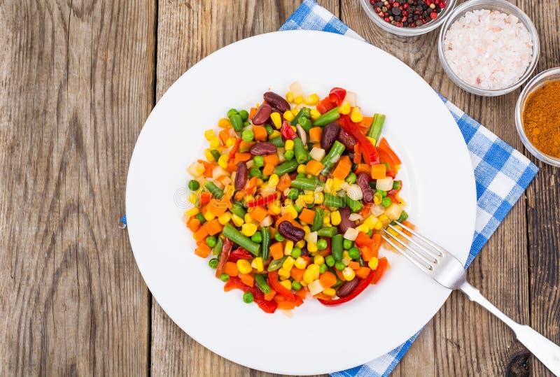 Βρασμένα λαχανικά στο άσπρο πιάτο στον παλαιό ξύλινο πίνακα Υγιές VE στοκ φωτογραφίες