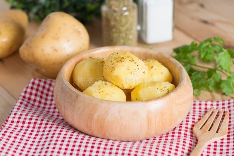 Βρασμένη πατάτα με oregano και άλας στο ξύλινο κύπελλο στοκ εικόνες