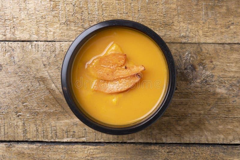 Βρασμένη σούπα κολοκύθας στο εμπορευματοκιβώτιο τροφίμων με το κουτάλι, έτοιμο γεύμα που τρώει στοκ εικόνα