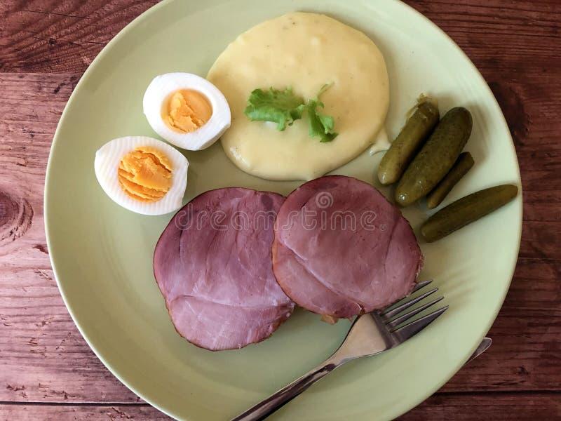 Βρασμένο ζαμπόν ή ζαμπόν διακοπών με τον πουρέ πατατών, τα αυγά Πάσχας και τα αγγούρια στοκ εικόνες