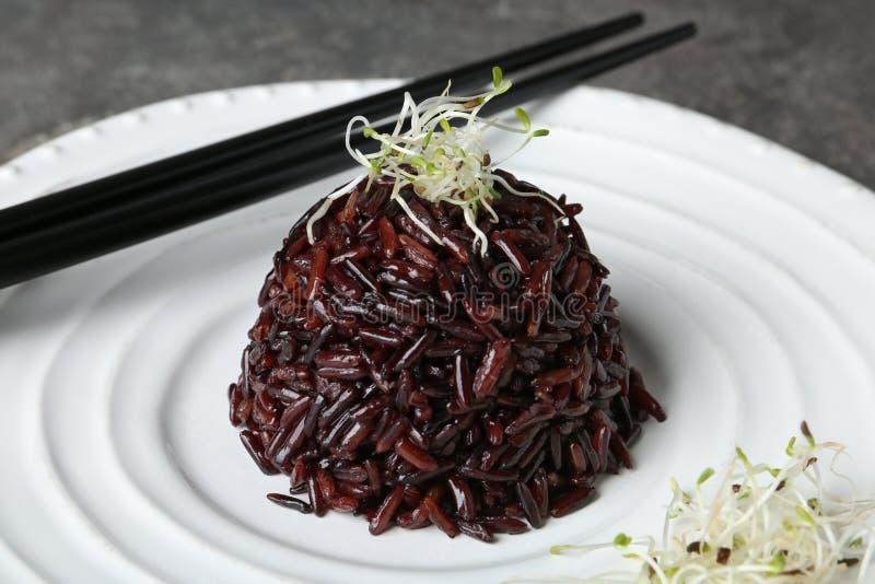 Βρασμένο καφετί ρύζι με τους βλαστημένους σπόρους λιναριού στο πιάτο στοκ εικόνα
