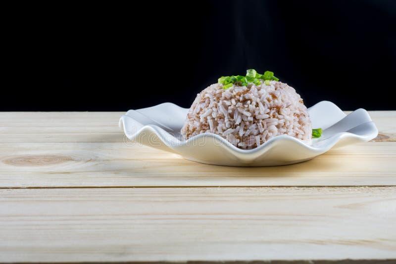 Βρασμένο ρύζι στο άσπρο πιάτο στον ξύλινο πίνακα στοκ εικόνες