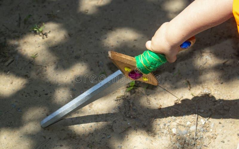 Βραχίονας μικρών παιδιών ` s με το ζωηρόχρωμο ξύλινο ξίφος παιχνιδιών σχετικά με το έδαφος με τις δραματικές σκιές στοκ εικόνα με δικαίωμα ελεύθερης χρήσης