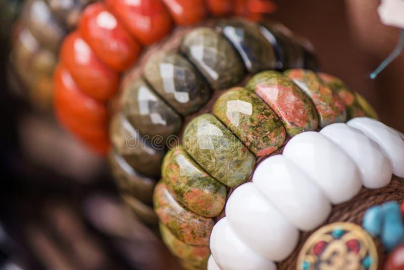 Βραχιόλια και περιδέραια πολύτιμων λίθων σε μια σειρά Κόσμημα φιαγμένο από κόκκινη ιάσπιδα, unakite πέτρες, obsidian πέτρες και ά στοκ εικόνες με δικαίωμα ελεύθερης χρήσης