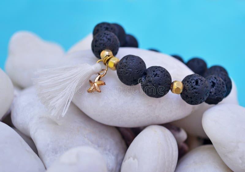 Βραχιόλι πολύτιμων λίθων με τις μαύρους χάντρες λάβας και τον αστερία κρεμαστών κοσμημάτων - πέτρες ηφαιστείων στοκ εικόνα