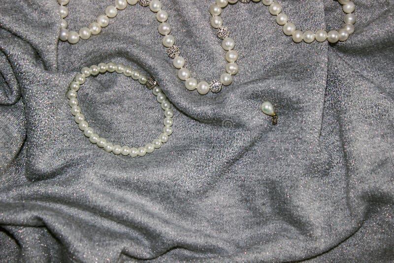 Βραχιόλι, χάντρες και κρεμαστό κόσμημα μαργαριταριών στο ανοικτό γκρι ύφασμα με τα κύματα και τα σπινθηρίσματα στοκ φωτογραφία με δικαίωμα ελεύθερης χρήσης