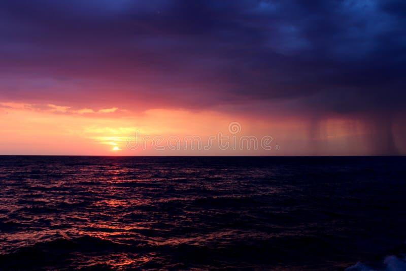 Βροχή πέρα από τη θάλασσα στο ηλιοβασίλεμα στοκ φωτογραφία με δικαίωμα ελεύθερης χρήσης