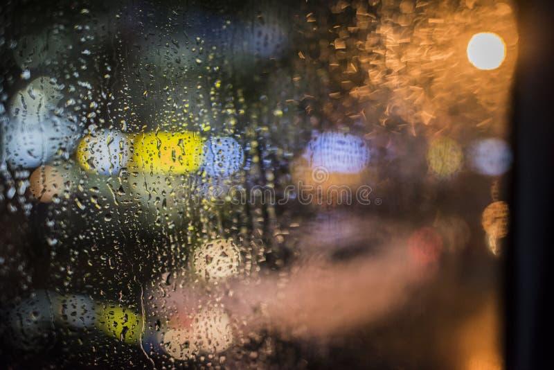 Βροχερή νύχτα, ελαφριά έξω από το παράθυρο λεωφορείων στοκ εικόνα