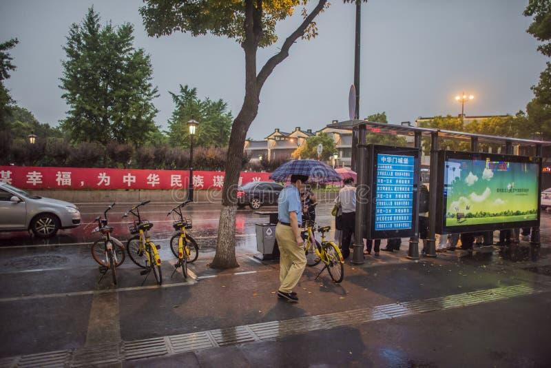 Βροχερή νύχτα, πεζοί στη στάση λεωφορείου που περιμένει το αυτοκίνητο στοκ εικόνες