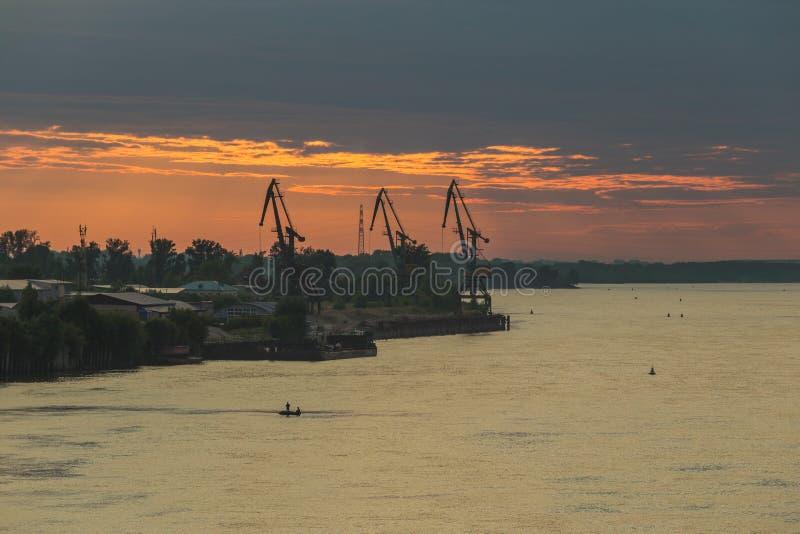 Βροχερός ουρανός πέρα από τον ποταμό Θλιβερός καιρός φθινοπώρου Σκιαγραφίες των γερανών φόρτωσης ποταμών στοκ εικόνα με δικαίωμα ελεύθερης χρήσης