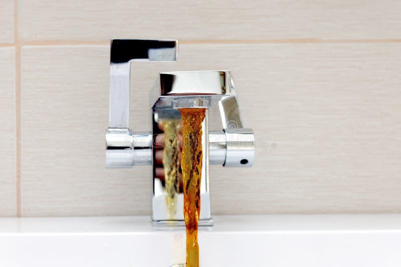 Βρύση χρώμιο-πιάτων με το σκουριασμένο, βρώμικο νερό στοκ εικόνες