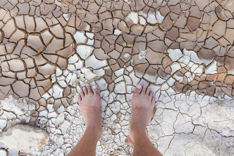 Βρώμικα γυμνά πόδια στο ραγισμένο έδαφος στοκ φωτογραφία