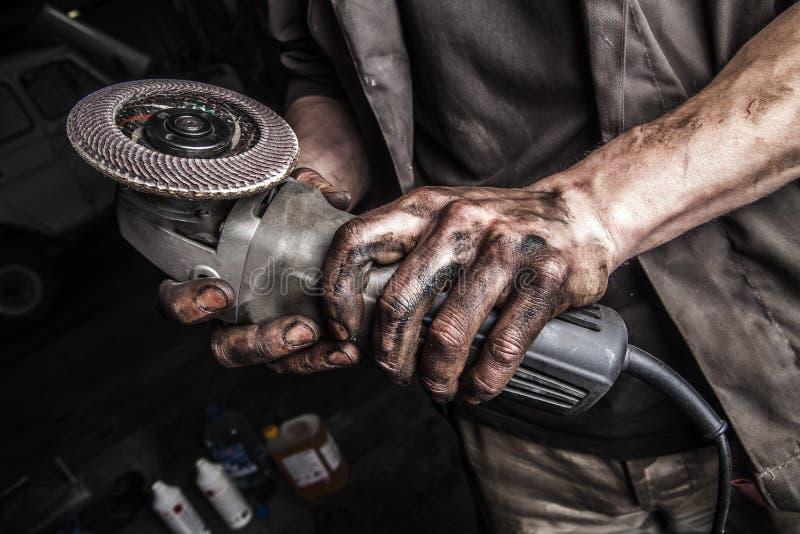 Βρώμικα χέρια με το μύλο γωνίας στοκ εικόνες