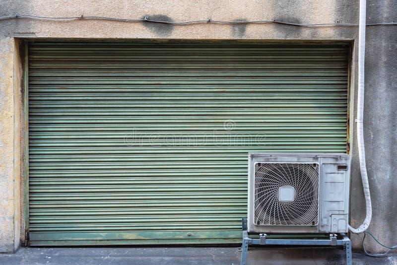Βρώμικη ξεπερασμένη μεταλλική πόρτα παραθυρόφυλλων κυλίνδρων με την παλαιά συμπυκνώνοντας μονάδα κλιματιστικών μηχανημάτων για το στοκ εικόνες