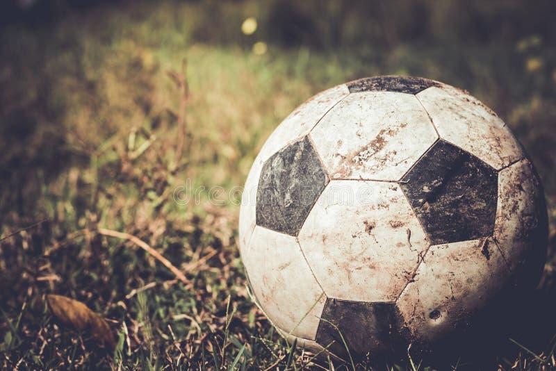 Βρώμικη σφαίρα ποδοσφαίρου στη χλόη στοκ φωτογραφία