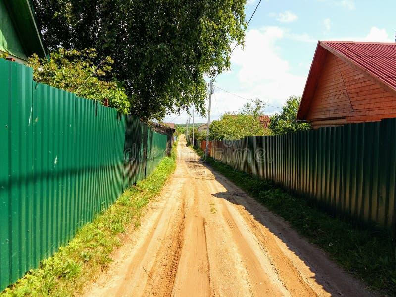 Βρώμικος δρόμος μεταξύ των περιοχών dacha, που περιφράζονται στοκ εικόνα με δικαίωμα ελεύθερης χρήσης