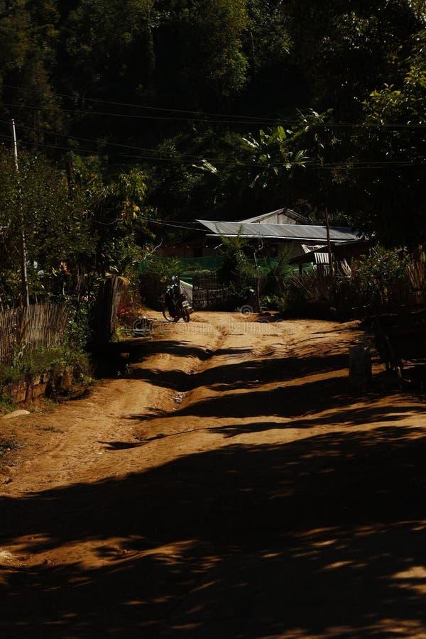 Βρώμικος δρόμος που οδηγεί μέσω ενός απομονωμένου χωριού στο Μιανμάρ, Βιρμανία στοκ φωτογραφία