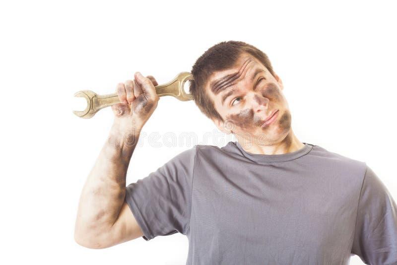 Βρώμικος και αστείος μηχανικός με το γαλλικό κλειδί που σκέφτεται απομονωμένος στοκ φωτογραφία με δικαίωμα ελεύθερης χρήσης