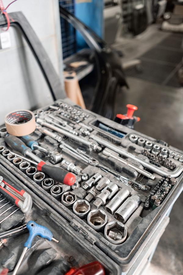 Βρώμικο σύνολο εργαλείων και wrenchs κινηματογράφησης σε πρώτο πλάνο χεριών στο κιβώτιο Χρωματίζοντας υπηρεσία αυτοκινήτων γκαράζ στοκ εικόνα με δικαίωμα ελεύθερης χρήσης