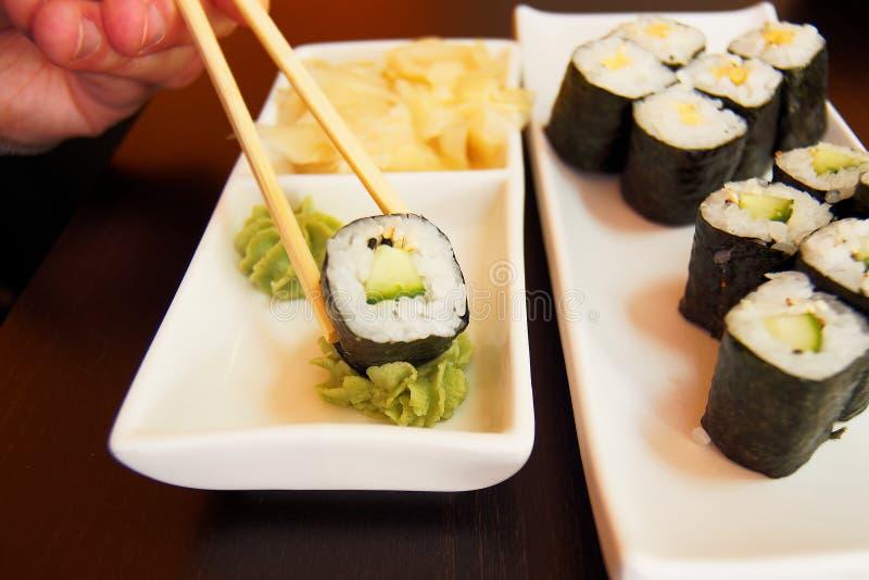Βυθίζοντας κάπα Maki στην κόλλα Wasabi στοκ φωτογραφίες με δικαίωμα ελεύθερης χρήσης