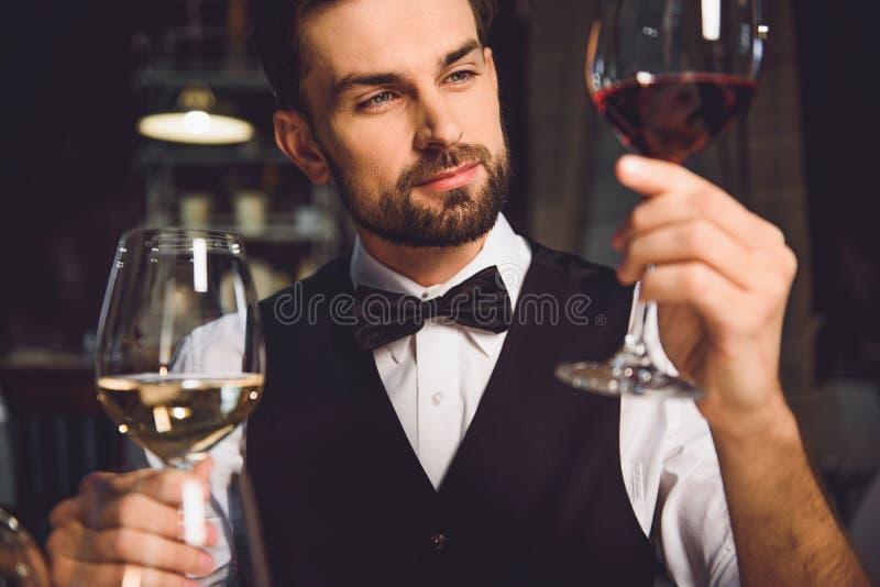 Βυθισμένος κριτικός οινοπνεύματος που κοιτάζει σταθερά στο κρασί στοκ εικόνες