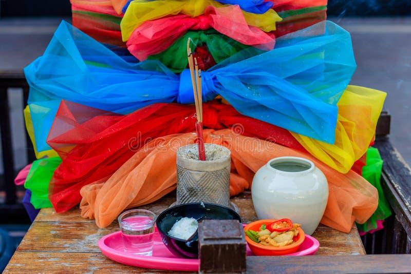 Βωμός οδών με τις προσφορές: το θυμίαμα, τα τρόφιμα και το νερό καψίματος, διακόσμησαν με τα τόξα του ζωηρόχρωμου υφάσματος bangk στοκ εικόνες