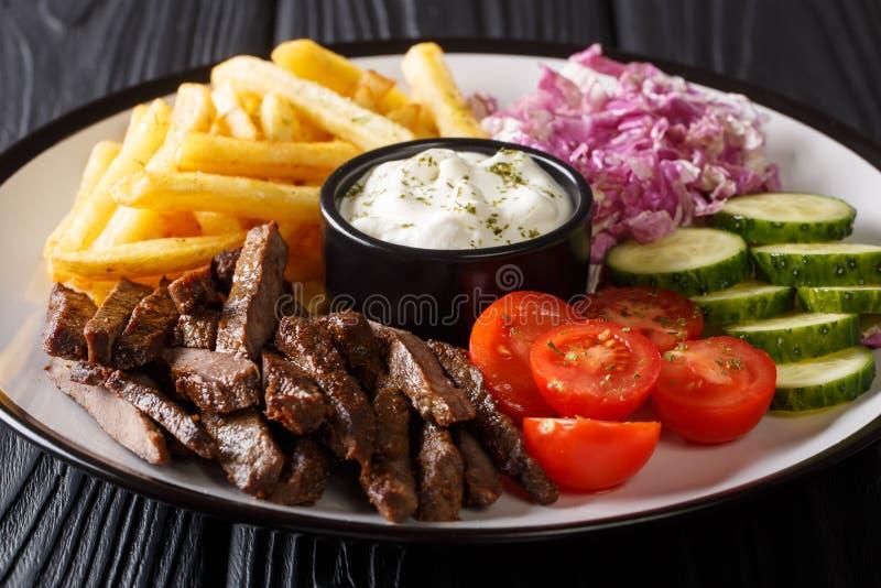 Βόειο κρέας Doner kebab σε ένα πιάτο με τις τηγανιτές πατάτες, την κινηματογράφηση σε πρώτο πλάνο σαλάτας και σάλτσας σε έναν πίν στοκ φωτογραφίες με δικαίωμα ελεύθερης χρήσης